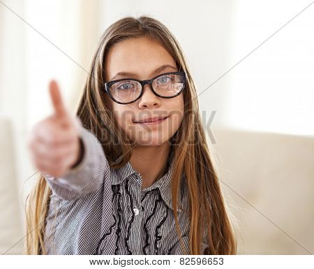 Portrait of 8 years old school girl wearing glasses looking at camera and showing thumb up