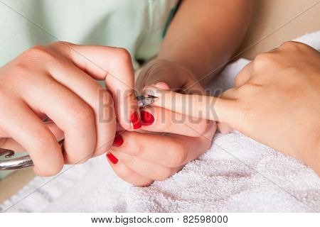 removing the cuticle at manicure beauty salon