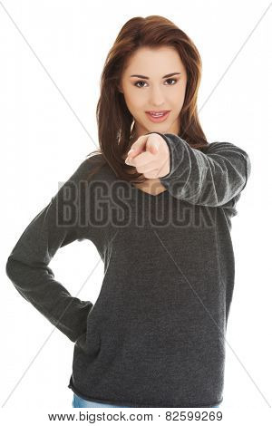 Young brunette woman pointing by a finger
