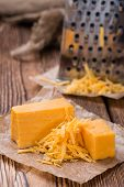 pic of grating  - Portion of grated Cheddar Cheese on rustic wooden background - JPG