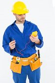 picture of multimeter  - Repairman examining multimeter while standing against white background - JPG