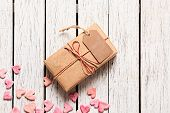 stock photo of wood craft  - Gift box with blank gift tag and heap of small hearts on white wooden background - JPG