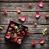 picture of rose  - Rose petals inside open gift box and scattered on old vintage wooden plates - JPG