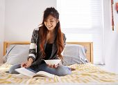 picture of healthy eating girl  - happy asian teen girl reading book and eating soup - JPG