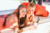 pic of sun-tanned  - Two woman lying in the sand on the beach - JPG