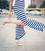 picture of slender legs  - Legs of woman with high heels dressed long striped dress outdoor in the city - JPG