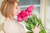 stock photo of pink eyes  - Beautiful girl with red hair and grey eyes,beautiful hair and a beautiful smile, is dressed in a light beige knitted sweater, holding a large bouquet of pink tulips,sitting in his office.