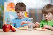 stock photo of kindergarten  - kids eating healthy food at home or kindergarten - JPG