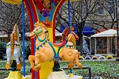 stock photo of carousel horse  - Colorful three horse carousel activated with coins - JPG
