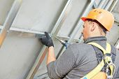 picture of tile cladding  - worker builder making construction for ventilation facade on a building with screwdriver drill - JPG