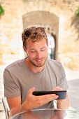 foto of internet-cafe  - Man using tablet 4g app working in outdoor summer cafe - JPG