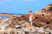 pic of aborigines  - cute boy with bamboo spear pretends like he is aborigine on desert island - JPG
