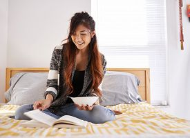 stock photo of tween  - happy asian teen girl reading book and eating soup - JPG