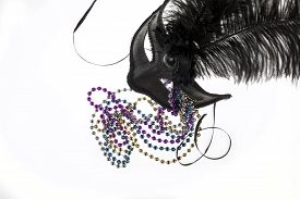 pic of debauchery  - Shiny gold purple blue and silver beads and Mardi Gras mask with feathers on a white background - JPG