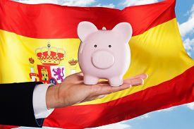 stock photo of spanish money  - Businessman Holding Piggybank In Front Of Spanish Flag - JPG