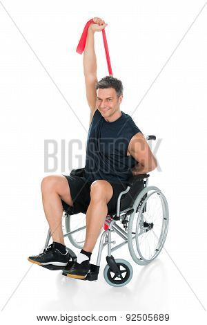 Disabled Man On Wheelchair Stretching With Resistance Band