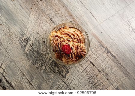 Ice Cream With Chocolate Crumb And Cherry On Wood Background