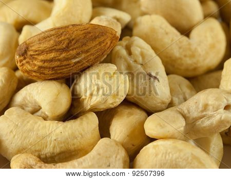 Standing out almond nut among cashew nuts