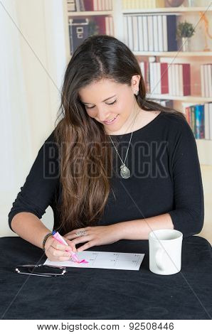 brunette girl sitting and writing on a paper