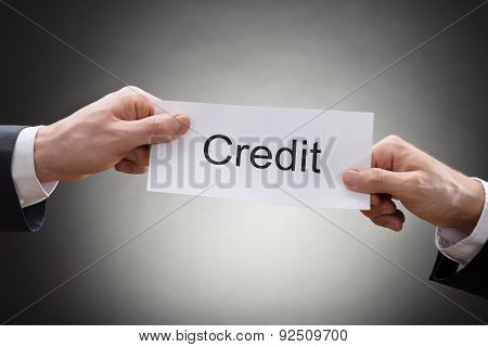 Close-up Of Two Hand's Holding Credit Paper