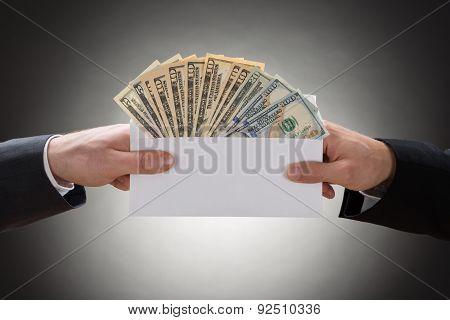 Close-up Of Hand's Holding Envelop Full Of Currency Note