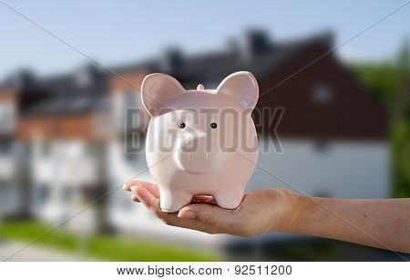 Woman's Hand Holding Piggybank. New House In Background