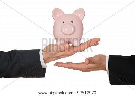Businessman's Hand Holding Piggybank