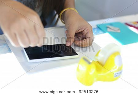 Woman Applying A Screen Protector On An Cellphone