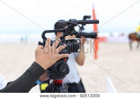 Cameraman Working On Recording On Beach Polo Tournament