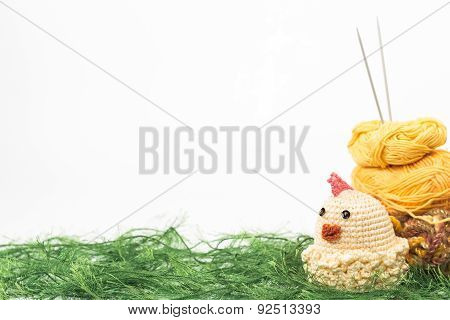 knitting toy chicken on a background of thread grass