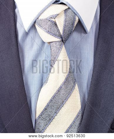 black suit and striped necktie with triple knot