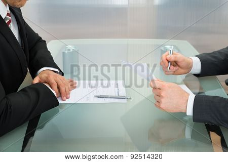 Businessmen With Application Form On Office Desk
