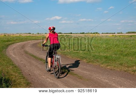 Young woman mountain bike ride on  dirt road. Ukraine