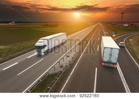 Two White Trucks In Motion Blur On The Highway At Sunset