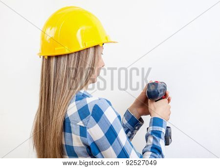 Young Woman Drilling A Hole In The Wall