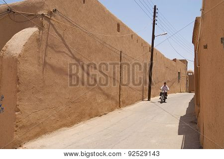 Man drives motorbike by the street of Yazd, Iran.