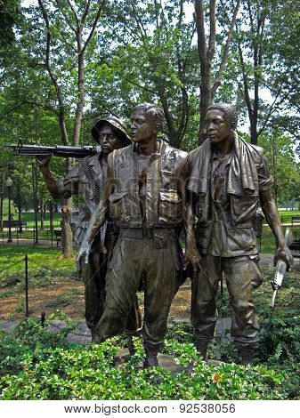 Washington D.C., USA - June 14, 2008: Statue of the three soldiers at the Vietnam Veterans Memorial in Washington D.C. that are looking on the roll of honour