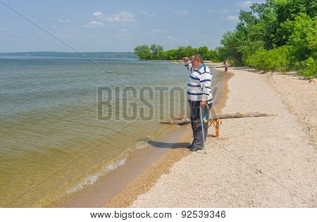 Senior man standing on the edge of the Dnepr river