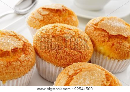 closeup of a pile of magdalenas, the typical spanish plain muffins, in a white plate on a set table with a cup of coffee or tea in the background