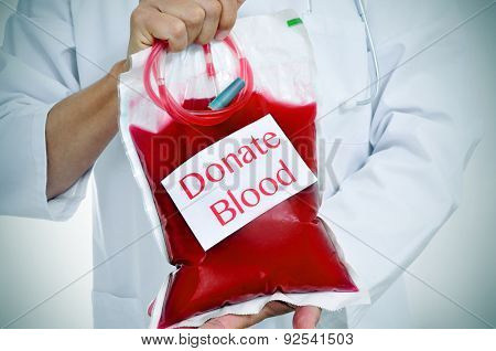 closeup of a doctor holding a blood bag with a sticker with the text donate blood