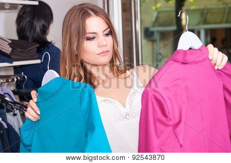 Teenage girl looking and choosing between two jackets