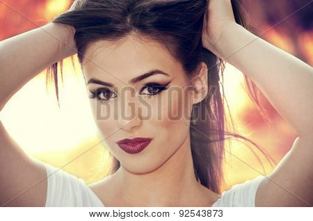 Beautiful young girl with hands in her hair with softly summer colors background
