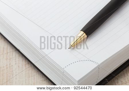 Notepad with ball pen on a wood background.
