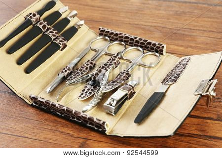 Manicure set in open case on wooden table, closeup