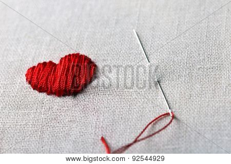 Canvas for embroidery and red sewing threads on table close up