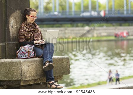 Female freelancer sitting outdoors with the laptop. Entrepreneur working with a laptop.
