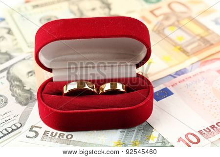 Wedding rings in box  on banknotes background. Marriage of convenience