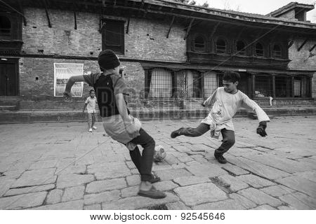 KATHMANDU, NEPAL - CIRCA DEC, 2013: Unknown children play football after lesson at Jagadguru School. School established in 2013, to let new generation learn Sanskrit and preserve Hindu culture.