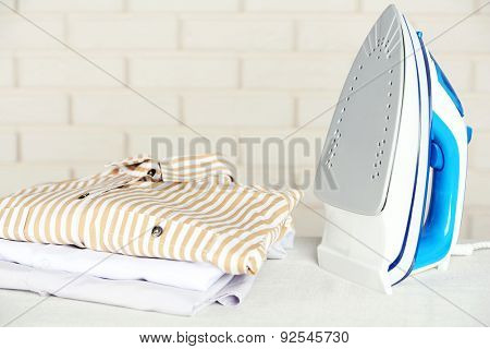 Pile of clothes and electric iron on brick wall background