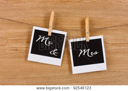 Photo papers hanging on the clothesline on wooden background